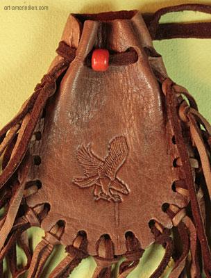 détail de l'aigle symbole américain décorant ce medicine bag amerindien avec franges de cuir